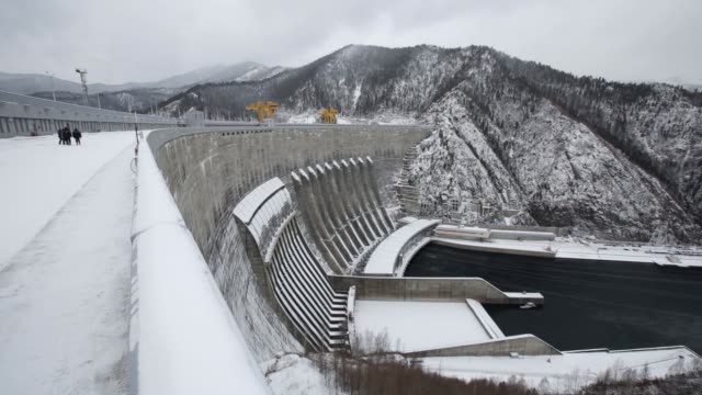 snow covers the sayanoshushenskaya hydropower station operated by oao rushydro as it stands on the yenisey river near sayanogorsk russia on friday... - energia idroelettrica video stock e b–roll