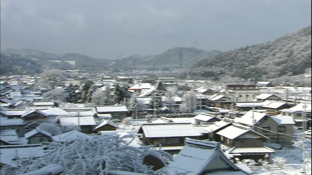 snow covers tile-roofed houses in japan. - shiga prefecture stock videos & royalty-free footage