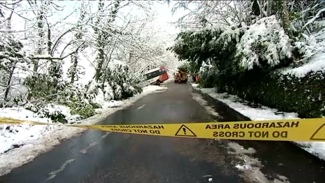 snow disruption across the uk south wales abercarn school coach halfway down embankment coach and rescue vehicle seen beyond cordon tape gvs traffic... - 非常線点の映像素材/bロール