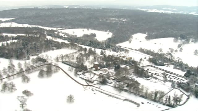 air views / aerials of snow covered countryside people sledging on box hill - サリー州 ボックスヒル点の映像素材/bロール