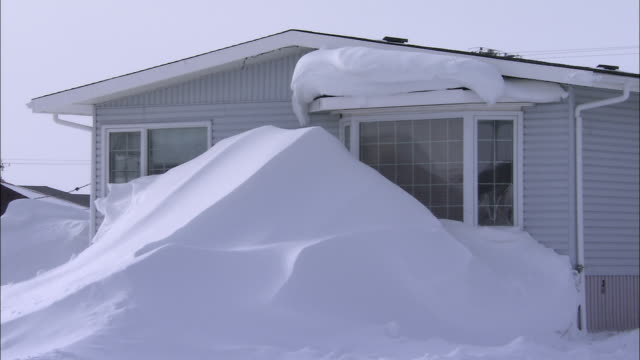 a snow drift reaches above windows on a house. - schneebedeckt stock-videos und b-roll-filmmaterial
