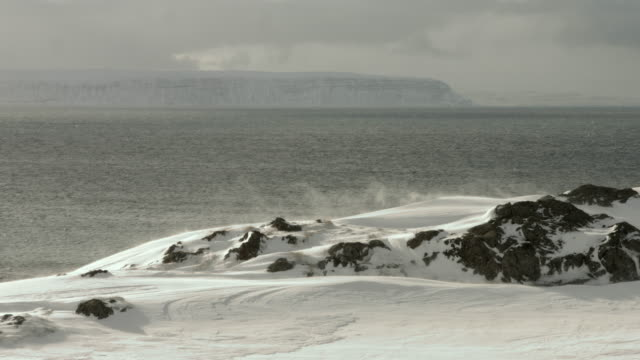 Snow drifts blow across the coastline of northern Iceland.