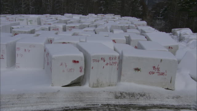 snow dusts blocks of granite at a quarry in vermont. - granite rock stock videos & royalty-free footage