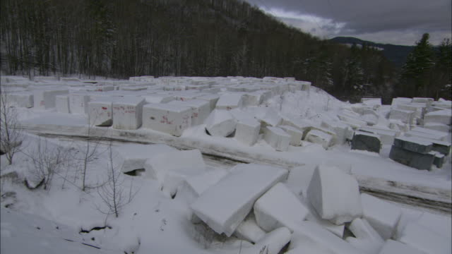 snow dusts blocks of granite that fill a quarry in the vermont mountains. - granite rock stock videos & royalty-free footage