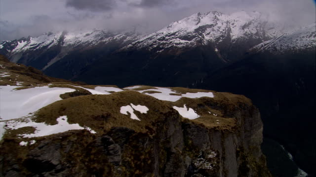 snow dusts cliffs and distant mountains in new zealand. available in hd. - queenstown stock videos & royalty-free footage