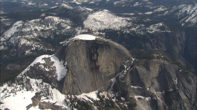 snow dusts half dome and the surrounding mountains and valleys of yosemite national park, california. - half dome stock videos & royalty-free footage
