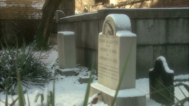 Snow dusts the tombstone of Edgar Allan Poe.