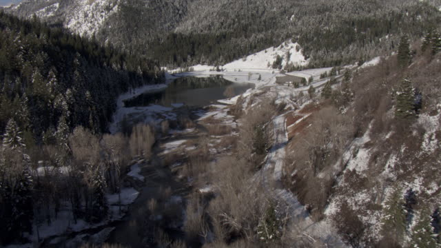 snow dusts wooded slopes that surround a meandering river in the wasatch mountains. - evergreen stock videos & royalty-free footage