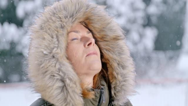 schnee fällt um heitere frau in fell kapuze, superzeitlupe, - kopf nach hinten stock-videos und b-roll-filmmaterial