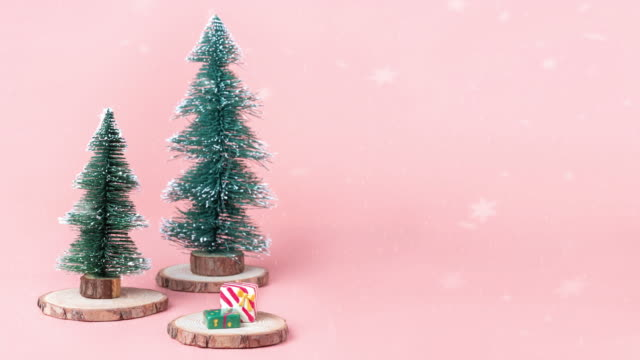 snow falling at Tree Christmas tree on wood log slice with present box on pastel pink studio background.Holiday festive celebration greeting card with copy space for display of design or content