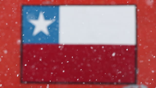 Snow falling in front of defocused Antarctic building with Chilean flag