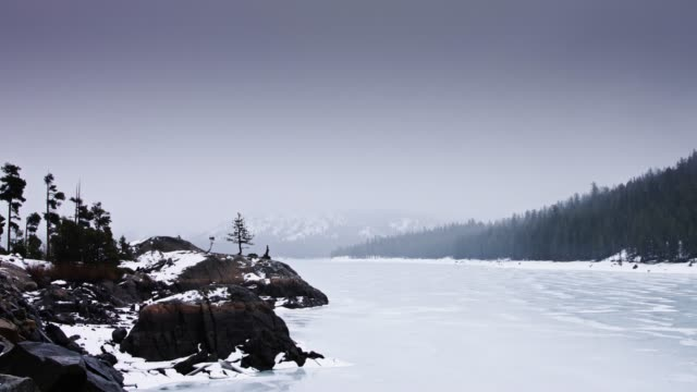 snow falling on frozen lake - californian sierra nevada stock videos and b-roll footage