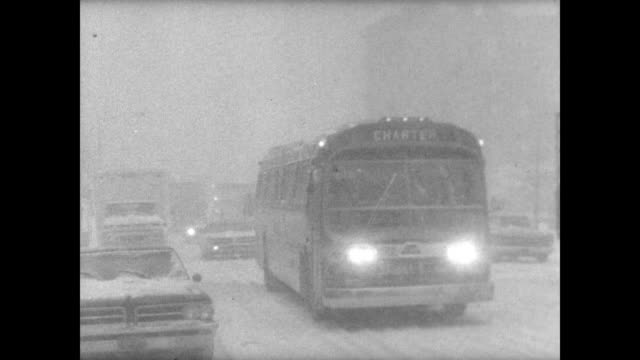 Snow falling on highway seen through blurry car window / city buildings mere outlines against snow and window view / man crosses street between...