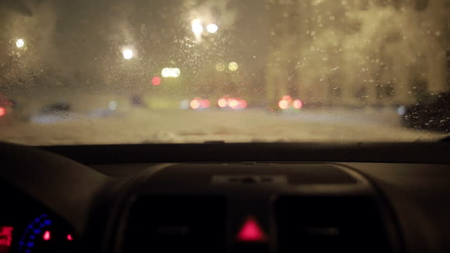 Snow falling on the windscreen and melting away.