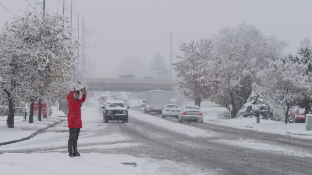 vídeos de stock, filmes e b-roll de snow falling on woman crossing busy urban street / orem, utah, united states,  - orem utah