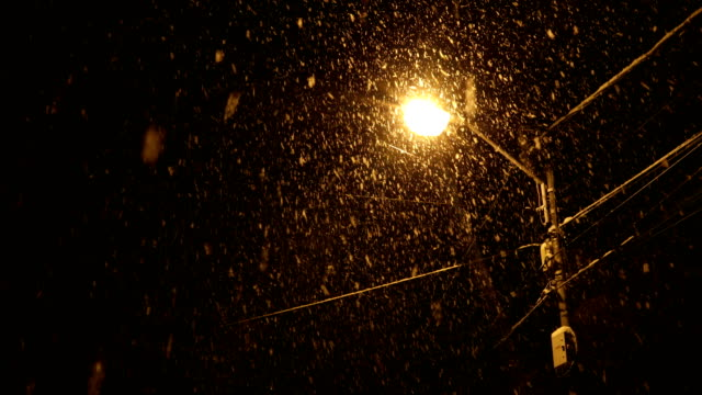 snow falling over a street lantern at night - street light stock videos & royalty-free footage