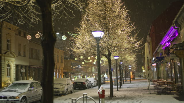 ms snow falling over christmas lights on main street at night - christmas tree stock videos & royalty-free footage