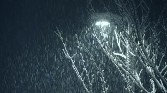 vídeos de stock, filmes e b-roll de neve caindo com lanterna de rua na noite - harmonia
