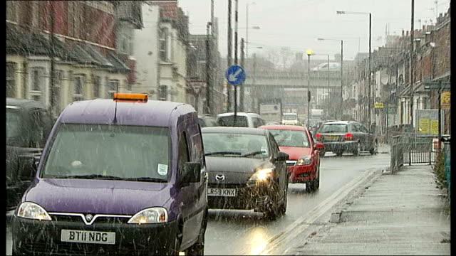 gritters: london fields lido; england: london: harrow: / london fields: ext / snow cars along roads in falling snow / people along in snow / cars... - harrow stock videos & royalty-free footage