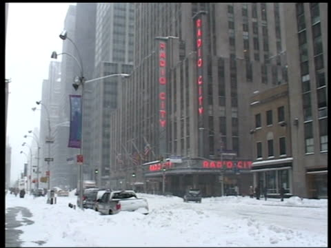 snow falls as cars pass radio city music hall amidst snow drifts manhattan - radio city music hall stock videos & royalty-free footage