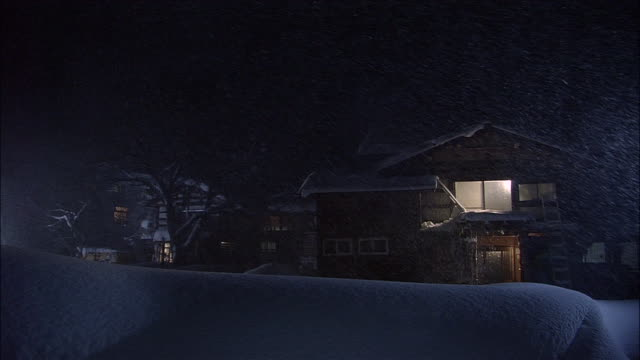 snow falls at night over houses, yokote, akita - schneebedeckt stock-videos und b-roll-filmmaterial