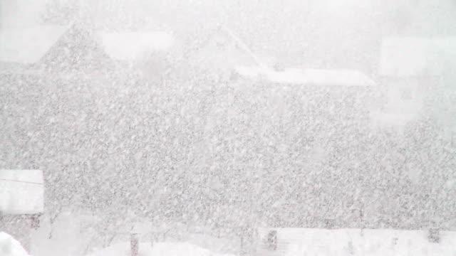 snow falls in a village. - schneeflocken stock-videos und b-roll-filmmaterial