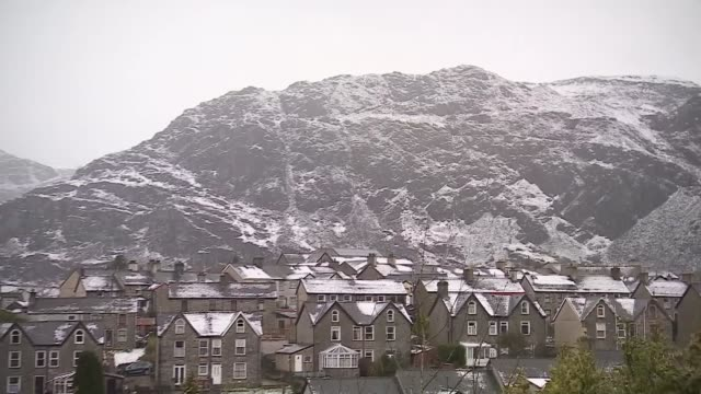 snow falls in parts of the country; wales: snowdonia: ext / snow snow on hilltops pull out snow on rooftops - snowdonia stock videos & royalty-free footage