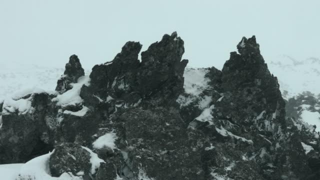 Snow falls on a jagged basalt rock at the Snaefellsnes peninsula.