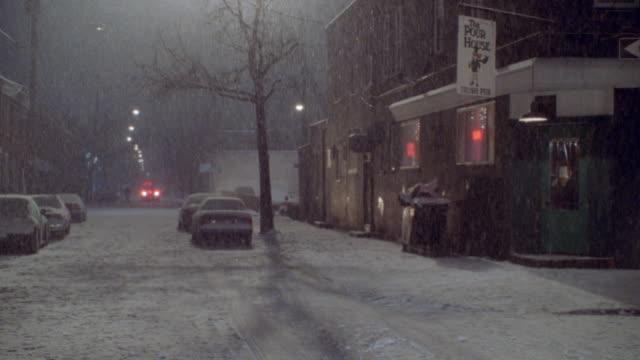 snow falls on a philadelphia, pennsylvania street at night. - street name sign stock videos & royalty-free footage