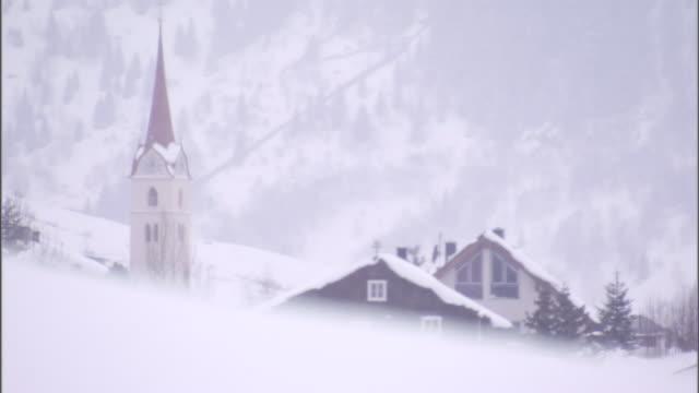 snow falls on a slope near a mountain town. - 尖り屋根点の映像素材/bロール