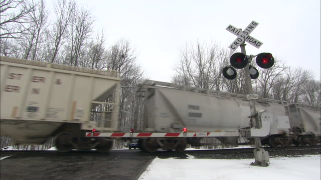 snow falls on a train traveling past a railroad crossing. - level crossing stock videos & royalty-free footage