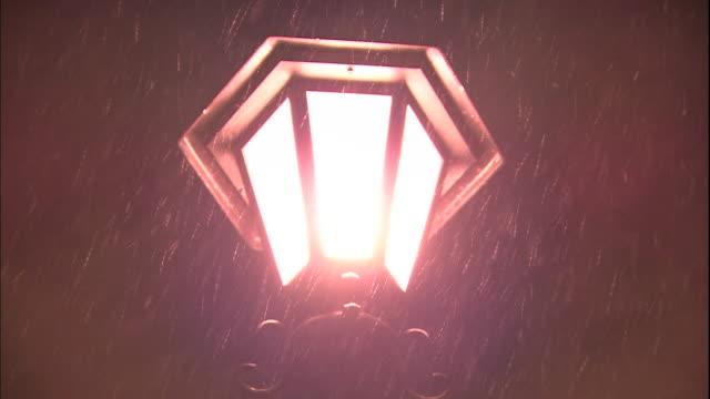 snow falls on an illuminated street lamp. - dissolvenza in chiusura video stock e b–roll