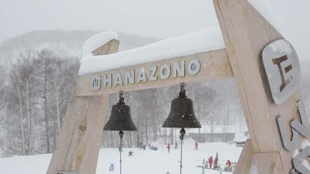 Snow falls on bells hanging at the base of the Niseko Hanazono resort sign operated by Nihon Harmony Resorts KK in Kutchan Hokkaido Japan on Sunday...