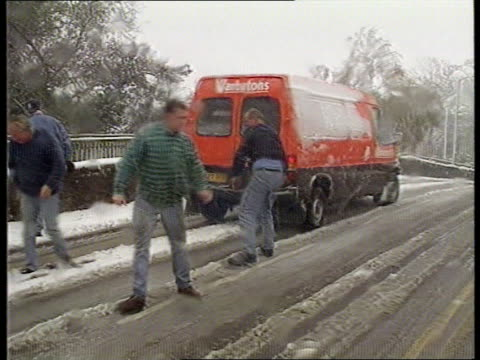 vídeos de stock, filmes e b-roll de snow falls on middle england htv lms men pushing van along road lms snow covered road signs pan rl to cars towards along snow covered road - empurrando