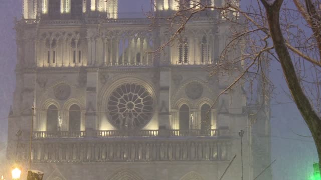 snow falls on paris's notre dame cathedral on tuesday as cold weather sweeps across france forcing 22 departments to activate a grand froid plan - cathedral stock videos & royalty-free footage