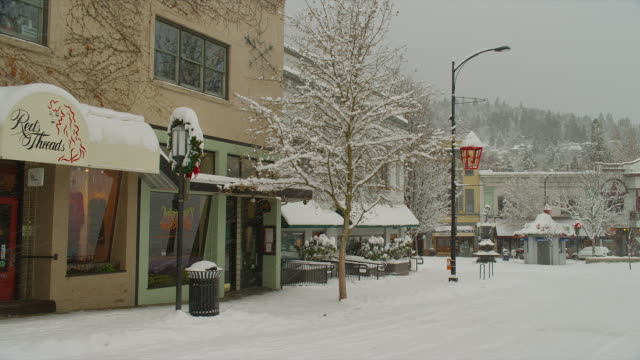vídeos de stock e filmes b-roll de medium pan snow falls on snowy street with christmas decorations in downtown ashland, oregon - lugar genérico