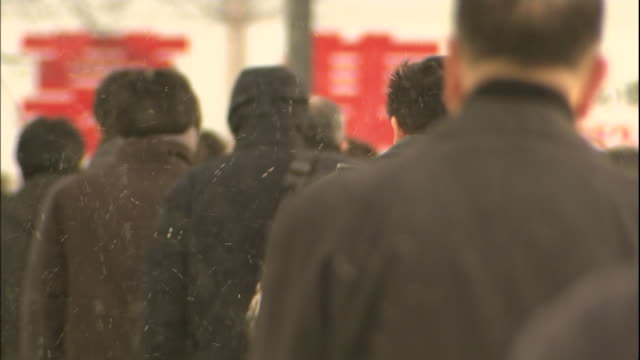 snow falls on the backs of pedestrians in morioka, japan. - warm clothing stock videos and b-roll footage