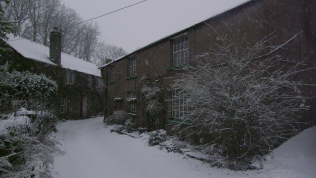 Snow falls onto country cottages and lane, Cumbria, England