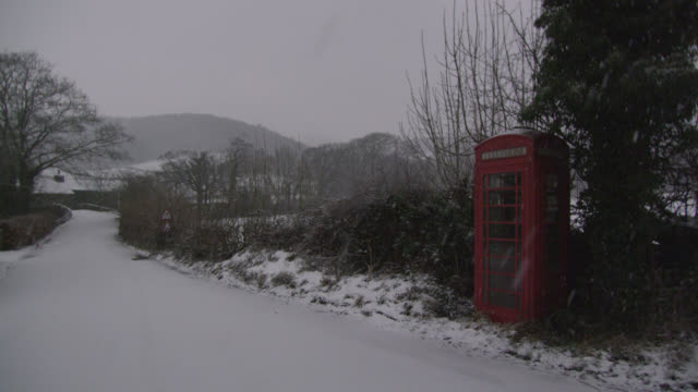 snow falls onto telephone box in country lane, cumbria, england - snowing stock videos & royalty-free footage