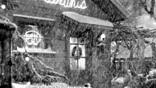 vídeos de stock e filmes b-roll de snow falls outside a cafe decorated for christmas. - 1946