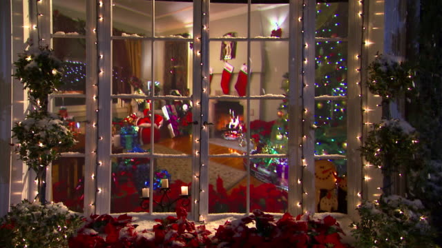 snow falls outside the window of a living room decorated for the christmas season. - stockings stock videos & royalty-free footage