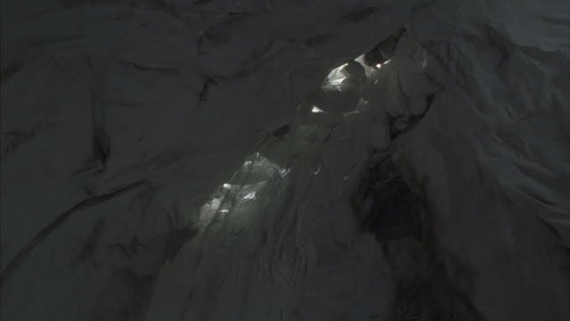 Snow falls through a crack in the ceiling of an ice cave.