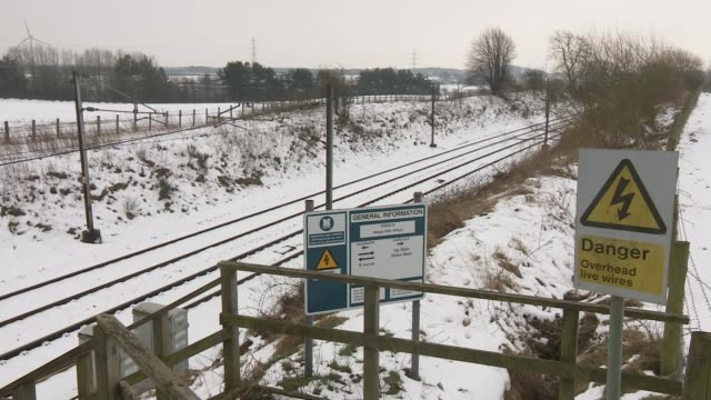 Further countrywide disruption as snow begins to thaw ENGLAND / SCOTLAND border Sign alongside West Coast Mainline railway track showing direction of...