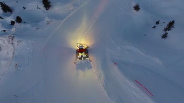 snow groomer preparing ski slope, aerial view - ゲレンデ点の映像素材/bロール