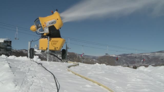 Snow gun makes manmade snow in Aspen while skiers can be seen in background