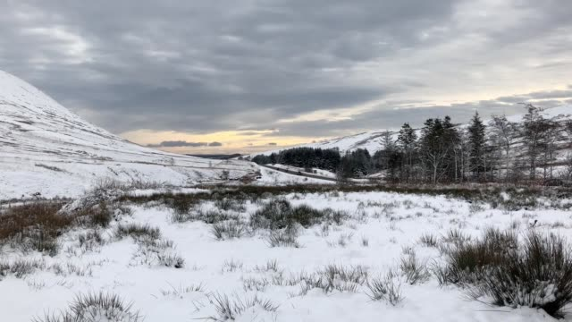snow has fallen across many parts of the uk with snowy scenes in brecon beacons in wales and divis mountain in belfast - ブレコンビーコンズ国立公園点の映像素材/bロール