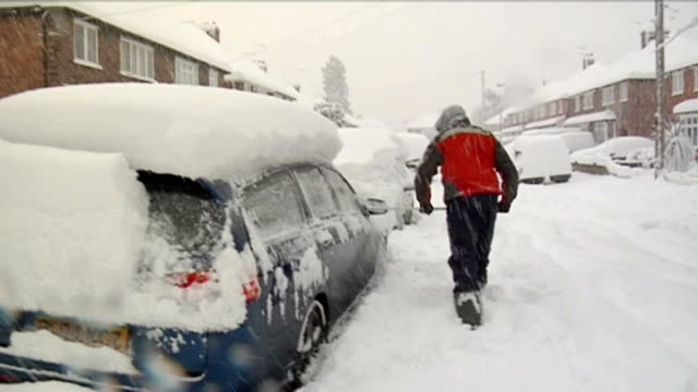 snow in surrey; england: surrey: guildford: ext/snowing man, using broom, to clear thick snow off car in suburban road another car revving engine as... - thick stock videos & royalty-free footage