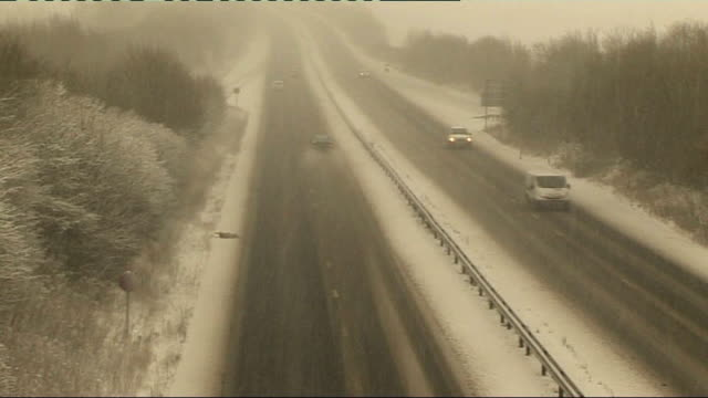 thames valley ext vehicles along dual carriageway as snow falling / car along roundabout / 'newbury east ilsley' road sign as snow falling / high... - newbury west berkshire stock-videos und b-roll-filmmaterial