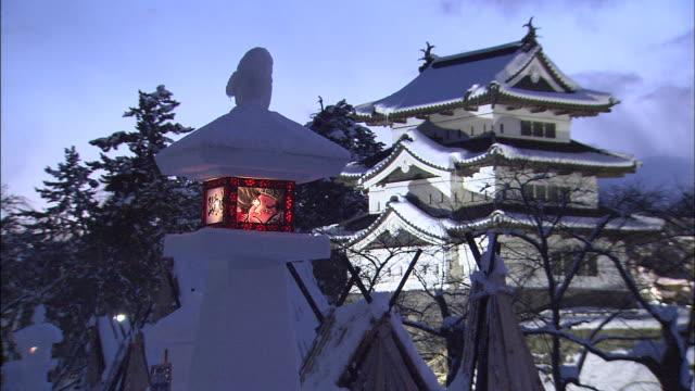 a snow lantern glows outside hirosaki castle during the snow lantern festival in hirosaki, japan. - aomori prefecture stock videos & royalty-free footage