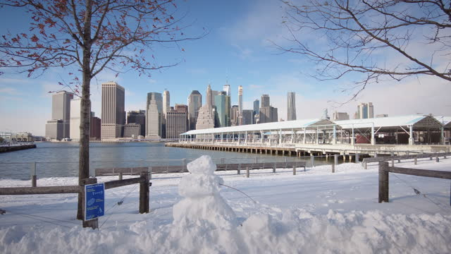 snow man. winter snow day in brooklyn bridge park with views onto lower manhattan. daytime, late afternoon. beautiful blue sky with clouds. filmed... - focus on foreground stock videos & royalty-free footage